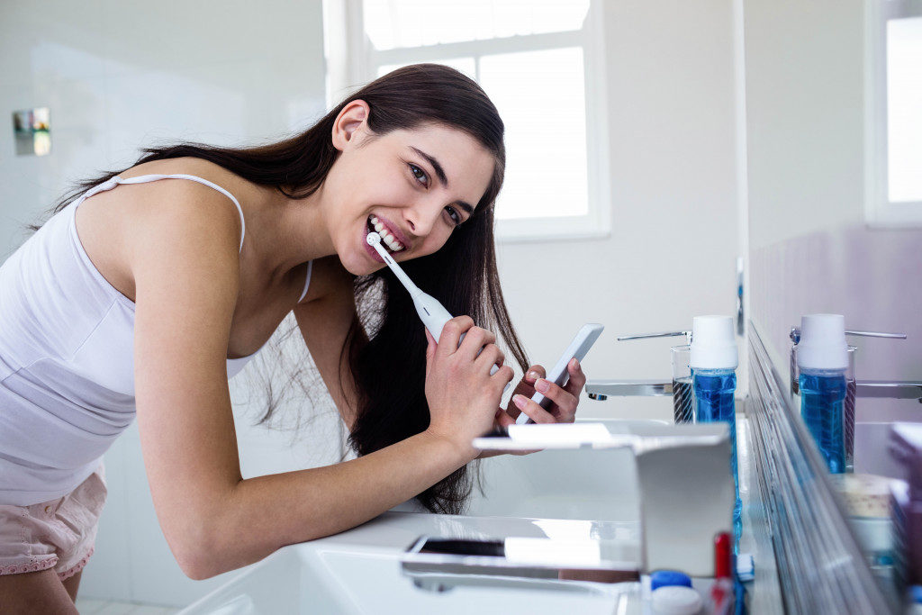 Female brushing teeth with electric toothbrush
