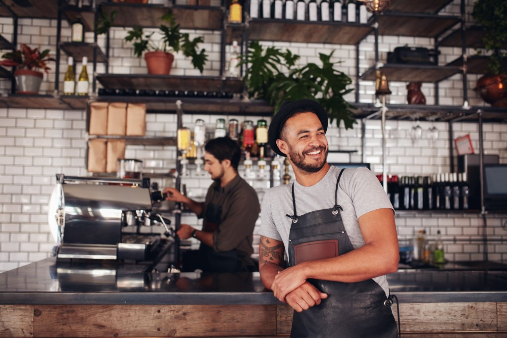man smiling inside coffee shop
