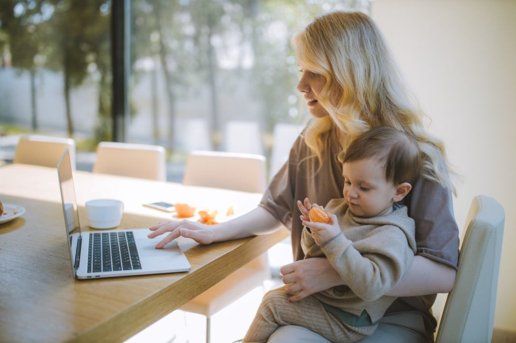 woman holding a baby while working
