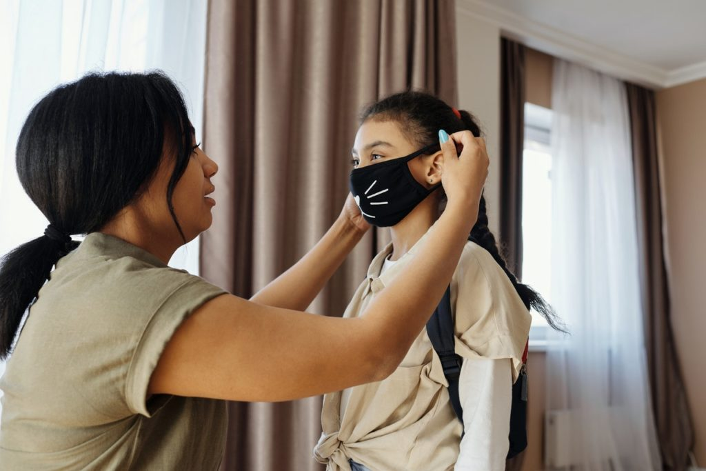 mother putting he daughter's mask on