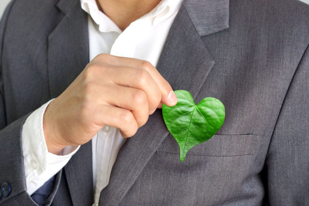 eco friendly concept holding heart shaped leaf