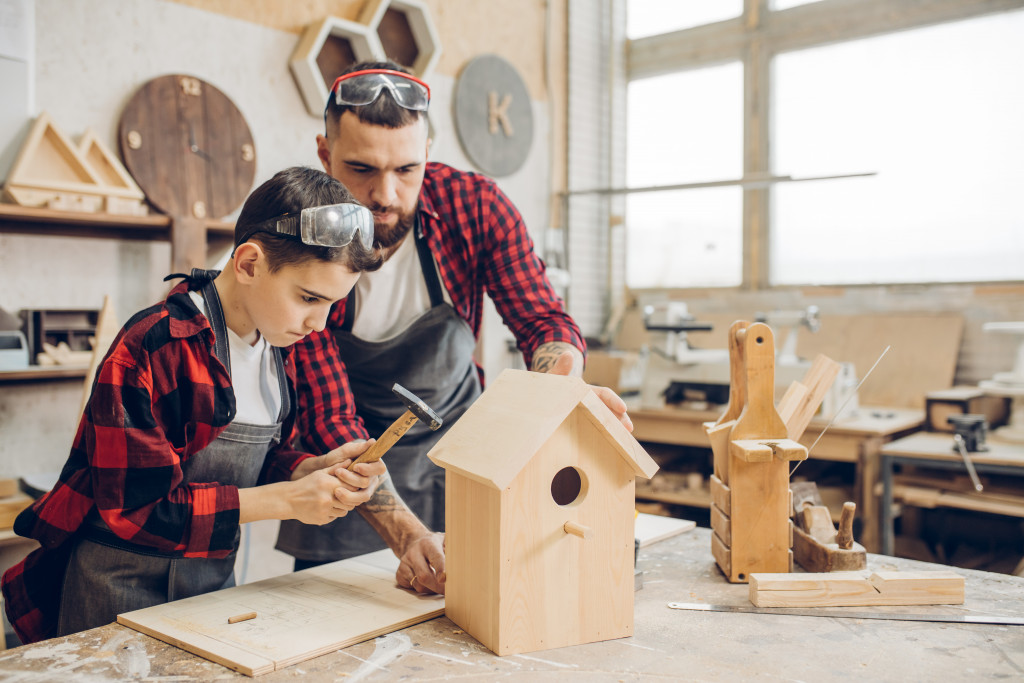 father and son building a birdhouse